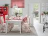 Stylowa jadalnia utrzymana wstylu prowansalskim. Dominującymi kolorami wtejaranżacji jest czerwień orazbiel.Niezwykle efektownie prezentują się krzesła ubrane wsukienki zkolekcji Avinon. Mocny akcent stanowi czerwony regał orazroleta rzymska zkolekcji Quadro.