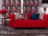Nowocześnie urządzony salon, któregogłównym punktem są tkaniny wintensywnych odcieniach, zkontrastowymi wzorami. Zasłony wkwiaty orazposzewki idealnie zesobą współgrają ipodkreślają nowoczesny charakter salonu. Czerwony pokrowiec nasofę zikea podkreśla gorący ienergetyczny charakter wnętrza. Wszystkie produkty pochodzą zinternetowego sklepu iinternetowej szwalni www.dekoria.pl